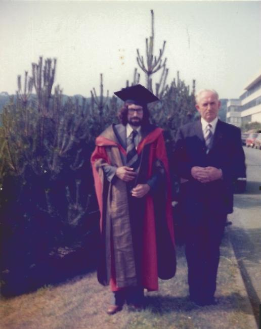 Myron posing in his Doctorate of Science gown alongside his father.